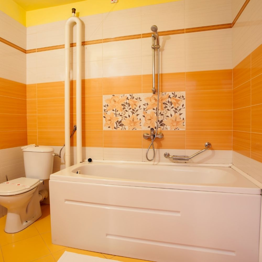 Country Bathroom With Orange And White Tile Wall