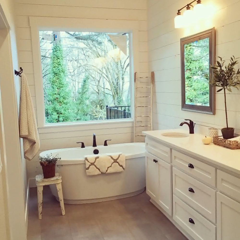 Country Bathroom With White Horizontal Wood Panel Wall And Rustic Stool