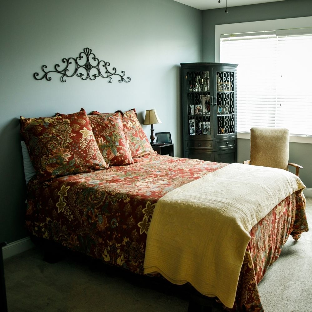 Traditional Bed With Red Floral Cushions And Sheets